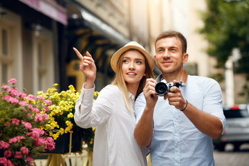Tourist Couple Taking Photos On Camera On Street.