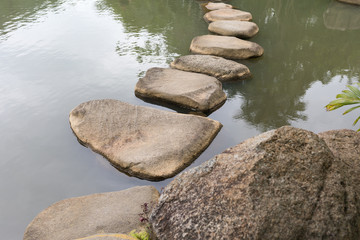 Bridge of stones on the surface of the lake in the YaNoDa tropical park in China on the Hainan Island