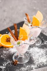 Vanilla Ice Cream With Fresh Mangoes on Black plate. Ice cream dessert, yogurt with orange slices, green mint leaves, cinnamon sticks on a dark stone tray and gray concrete background.