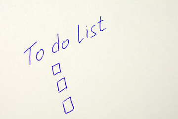 to do list on a white sheet of paper, pen notes completed check box. self management concept, close up, selective focus