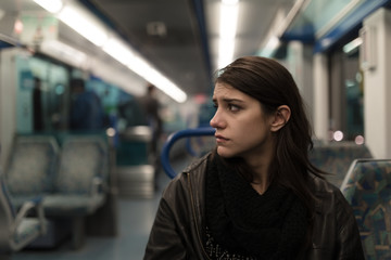 Sad depressive woman in train going home from work.Tired exhausted looking young lady getting away with train ride.Bored female person during commute time.Public transportation user.Using mobile phone