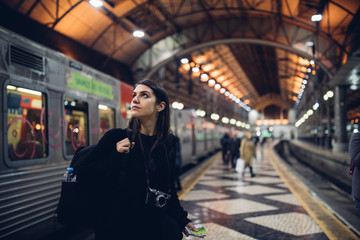 Female traveler searching for directions,waiting for the train/tram,using transportation in foreign country.Urban tourism.Low budget cheap ticket backpacking.Travel to the destination