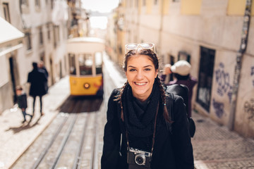 Young cheerful woman walking down the street of Lisbon.Amazed tourist visiting Europe off season during winter.Student in Portugal,Europe on a spring brake trip exploring big cities.Positive female
