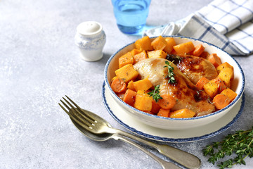 Roasted chicken legs with pumpkin and carrot.