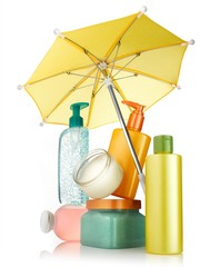 Plastic lotion bottles with yellow umbrella on white background