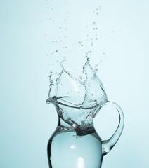 Water splashing into glass pitcher