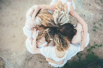Overhead view of five young women hugging in a circle