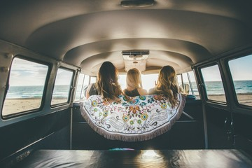 Rear view of three young women inside a vehicle at the beach