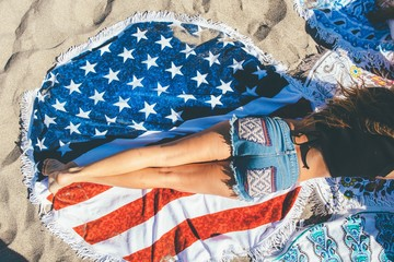 Overhead view of a young woman reclining on American flag beach towel and wearing denim shorts