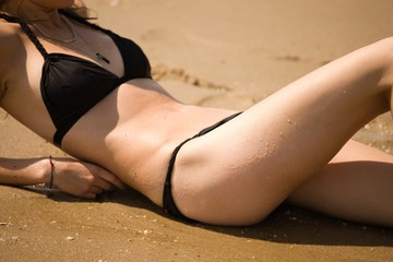 Young woman wearing black bikini and reclining on beach