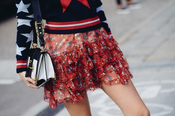 Midsection of young woman wearing red ruffled skirt and holding a purse