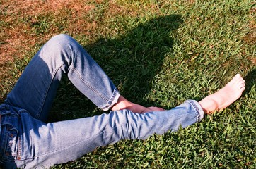 Legs of barefoot young woman wearing denim jeans and reclining on grass