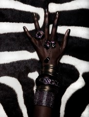Close up of woman's hand wearing rings, golden bracelets and amethyst jewelry