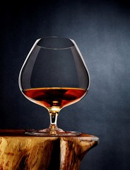 Alcohol in brandy glass on wood tabletop