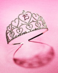 Quinceanera tiara decorated with number 15 in hearts against pink background