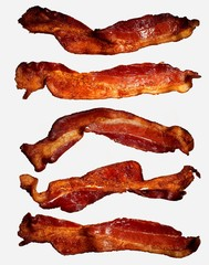 Five strips of crispy cooked bacon against white background