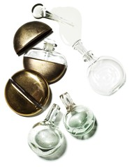 Glass and metal perfume bottles spilling liquid against white background