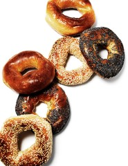 Six varieties of bagels against white background