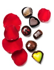 Pieces of chocolate candy and red rose petals