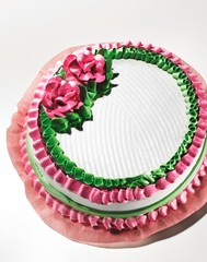 White cake decorated with pink frosting flowers and green icing against white background