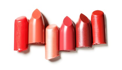 Close-up of six red lipstick pieces against white background