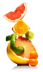 Close-up stack of fresh citrus fruit slices and wedges against white background