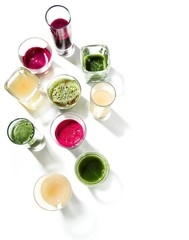 Top view of wheatgrass juice, kale and fruit smoothies in glasses
