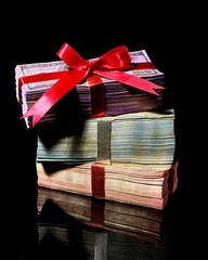 Stack of currency bills tied with red ribbon bow on black background