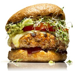 Chicken patty burger with cheese and alfalfa sprouts on bun