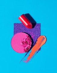 Red lipstick and crushed powdered cosmetics on blue background