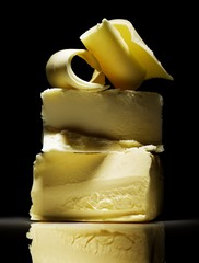 Stack of butter pieces against black background