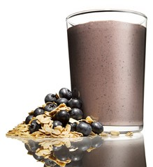 Close up of blueberry smoothie and fresh blueberries with granola