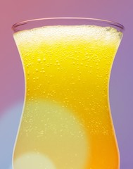 Close up of yellow drink with bubbles in glass