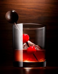 Cocktail glass with cherries and drink stirrer
