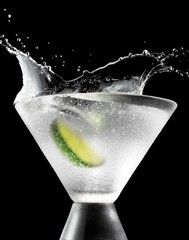 Lime slice splashing into drink glass