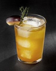 Cocktail with fruit slice garnish and thyme sprig