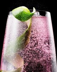 Low angle close-up drink with bubbles and lime peel