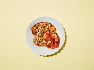 Plate of French toast with bananas, almonds and fruit jam
