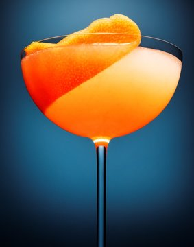Low angle close-up view of orange cocktail in glass with orange peel garnish