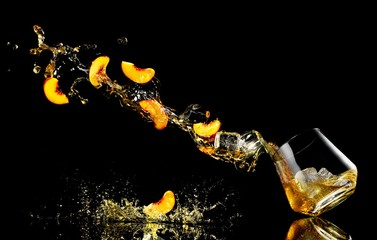 Slices of peaches and liquid falling into cocktail glass against black background