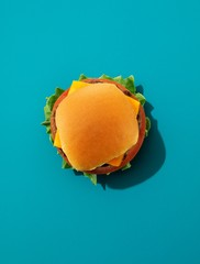 Top view of cheeseburger and bun against blue background