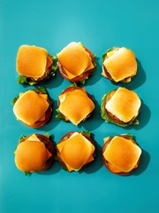 Top view of cheeseburgers and buns against blue background