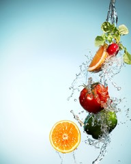Fruits and vegetables splashed in falling water