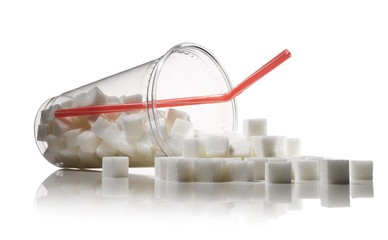 White sugar cubes spilling out of plastic cup with drinking straw against white background