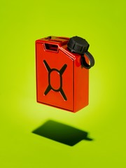 Red plastic gas can against green background