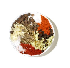 Bowl of powdered curry spices with seeds and garlic