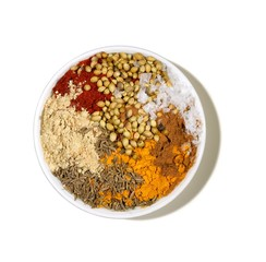 Bowl of powdered curry spices with seeds and turmeric
