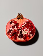 Cross section of pomegranate filled with red vitamin capsules