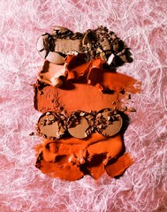 Orange lipstick pieces and crushed brown powdered cosmetics