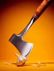 Axe blade chopping garlic clove
